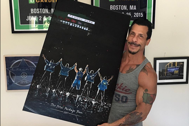Danny Wood holding a painting about NKOTB at Fenway Park