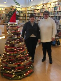 Two women stand next to a Christmas tree made from stacked books