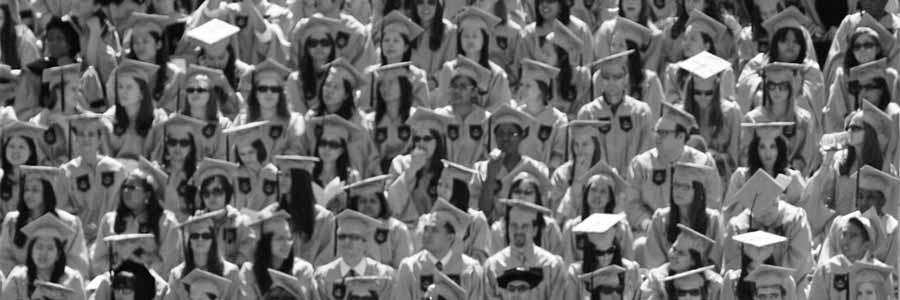 bleachers filled with graduating students in academic regalia