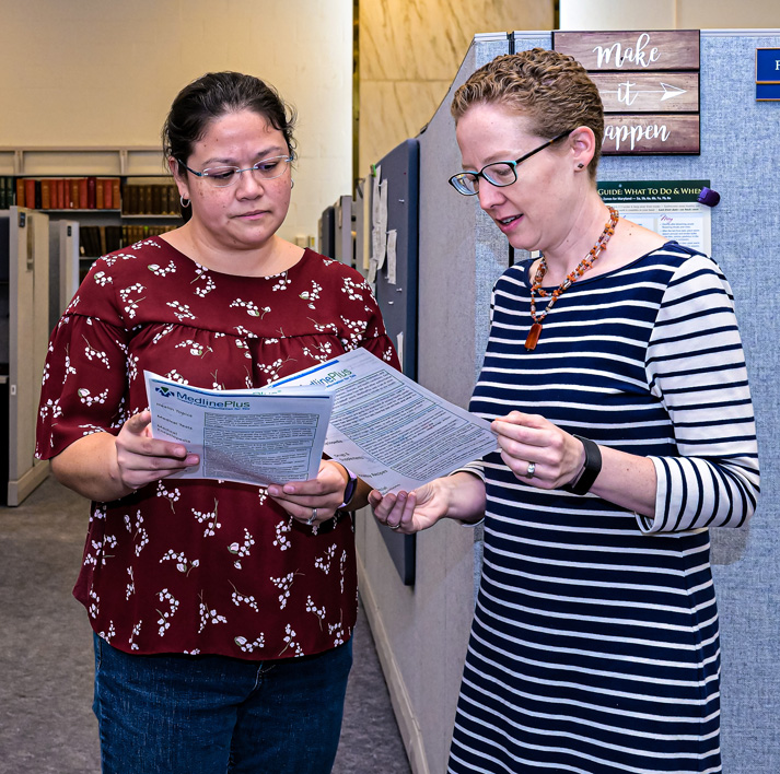 Two NLM employees in discussion about MedlinePlus.