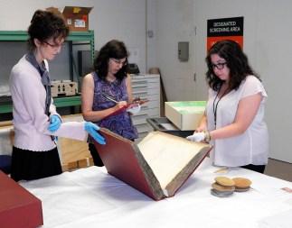 Three women examine a large book.