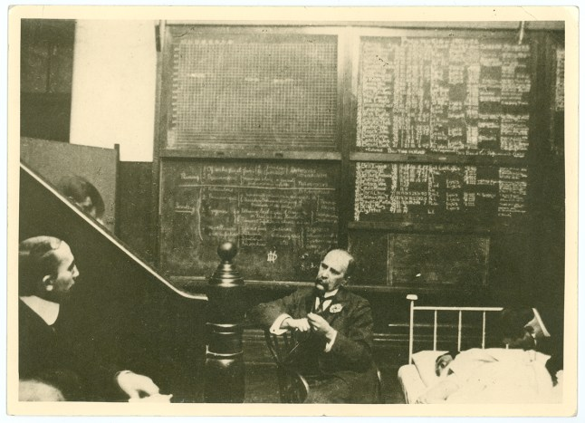 Osler, in conversation with others, seated next to a patient in a bed, behind him are blackboards covered in close writing.