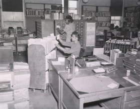 Librarians file books and catalog cards in a room crowded with desks and book carts.
