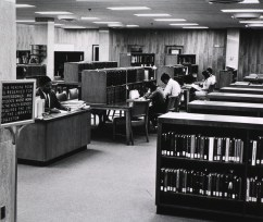 A staff member works at a desk while patrons work in a library reading room.