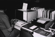 A woman types a search into a specialized terminal.