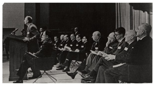 A man speaks at a podium while many others, seated on stage behind him, look on.