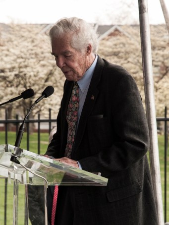 Dr. Lindberg speaks at a podium on the lawn of the National Library of Medicine.