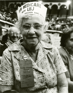 An older woman smiles at the camera wearing a paper hat that reads WIN MEDICARE with LBJ, Golden Ring Council.