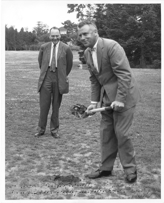 Fogarty lifts the first shovel of dirt while another man looks on.