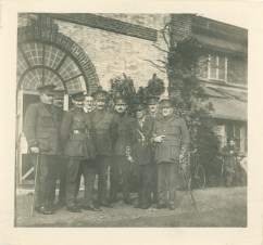 A group of men in uniform stand outside on the grass in front of a building.