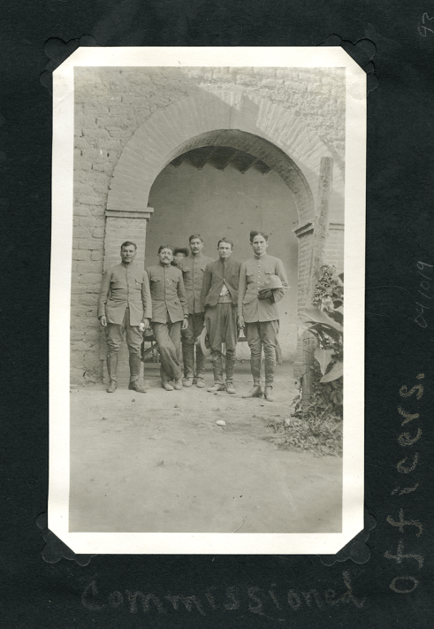 Five men in uniform pose outdoors by a brick archway.