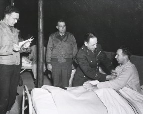 In a U.S. Army hospital, Mr. Milton D. Cohn, National Commander of the Disabled Veterans Organization, pins the Purple Heart on Private Earl Webb
