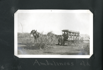 A team of four horses pulls an open canvas covered wooden wagon marked with U.S. and a cross.
