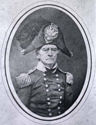 Photographic portrait of an older man in military uniform including a cocked hat with plume.