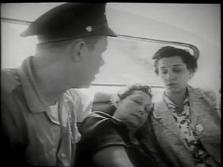 A policeman rides in the back of a car with a woman and an unconsious woman.