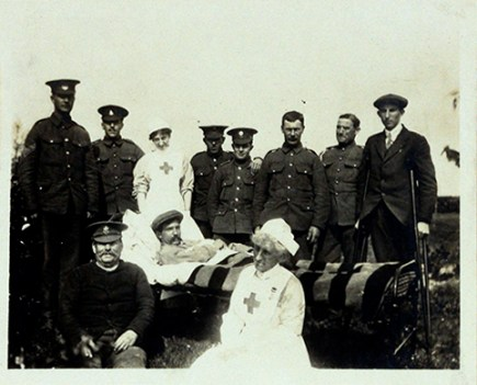 Outdoors, a posed group of men in uniform and two nurses surround a man in a bed.
