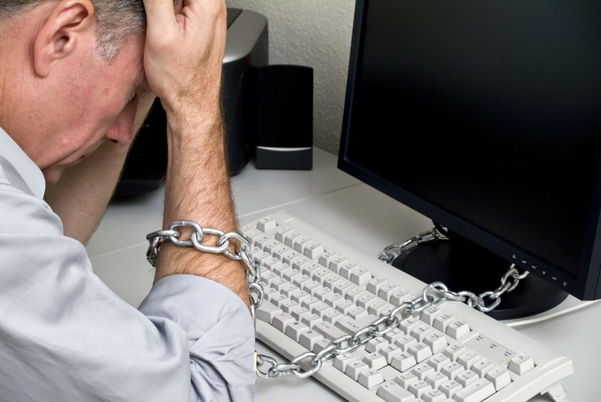 1326954 - a man feeling as if he is chained to his computer doing a job with no future.