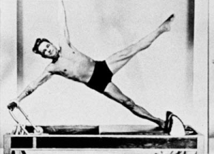 Joseph Pilates, pictured exercising on a Reformer machine