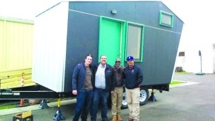 Truck driver Martin Kauffman (far left) and electrician Art Ramirez (far right), who both donated their services to deliver Laney College's tiny home prototype to West Side Missionary Baptist Church, stand in front of the Pocket House Model M with Rev. Ken Chambers (middle right) and Councilmember Abel Guillén (middle left).