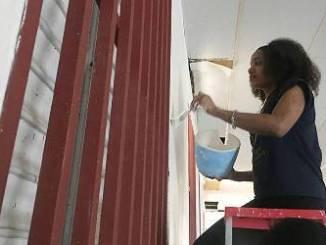 Raisa Dorsaindville, 20, paints a wall inside La Hermosa Church in downtown Arecibo, Puerto Rico. (Tatyana Hopkins/NNPA)