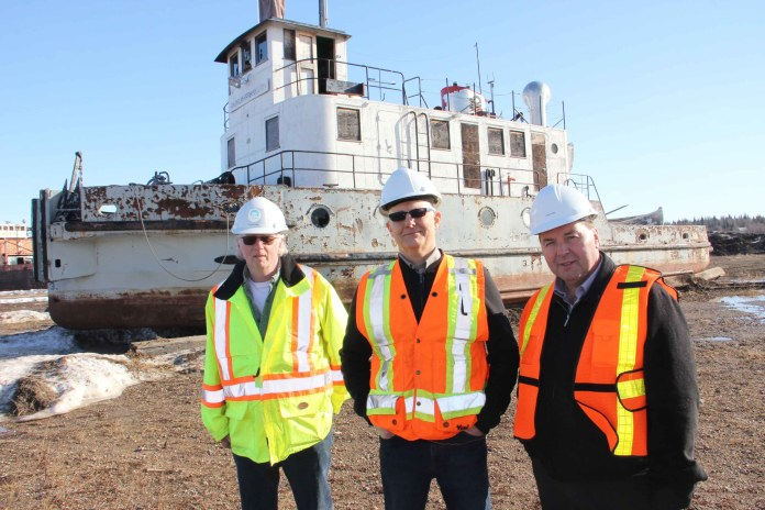 The Radium Franklin is being donated to the Hay River Museum Society by the GNWT's Department of Infrastructure. Standing in front of the vessel at the Marine Transportation Services Shipyard in Hay River on March 22 are, left to right, John Vandenberg, the assistant deputy minister of Infrastructure; Pat Williams, the assistant director of Marine Transportation Services; and Infrastructure Minister Wally Schumann. Paul Bickford/NNSL photo