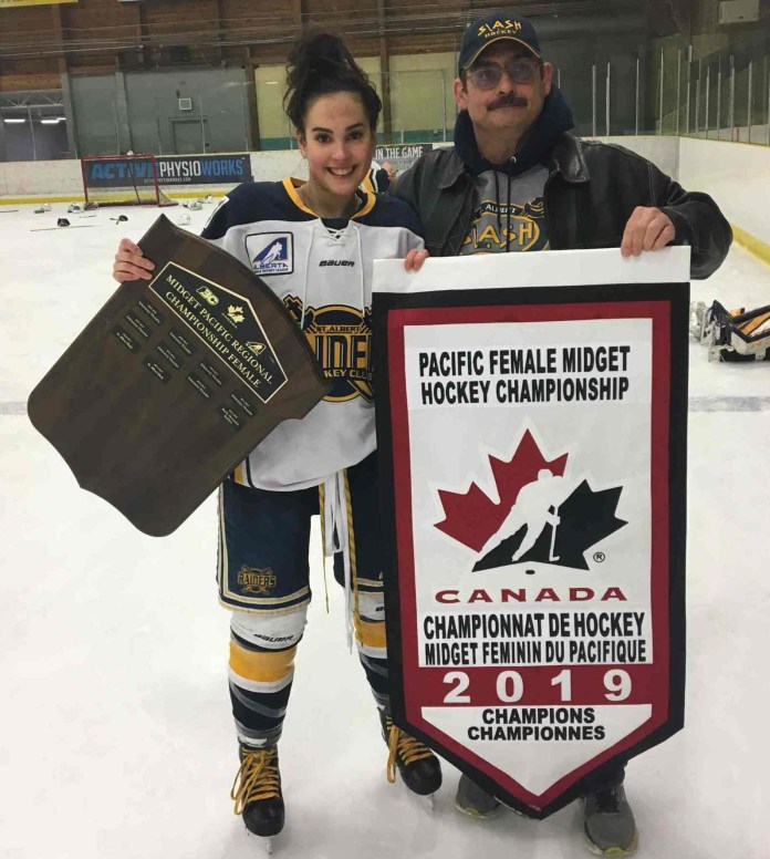 Kiah Vail, left, shows off the championship banner her St. Albert Slash won on home ice on April 7 with her father, Roger Vail. photo courtesy of Roger Vail
