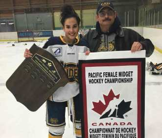 Kiah Vail, left, shows off the championship banner her St. Albert Slash won on home ice on April 7 with her father, Roger Vail. She can now add the title of national champion as the Slash knocked off the Sudbury Lady Wolves of Ontario to win the Esso Cup on April 27, the third consecutive year the Slash have won the Canadian midget girls hockey championship. photo courtesy of Roger Vail