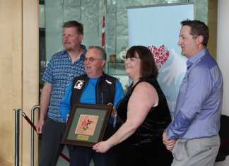 The board of the 2018 South Slave Arctic Winter Games was recognized on May 24 in Yellowknife with an Outstanding Volunteer Award from the GNWT. At the presentation were, left to right, Fort Smith's Kevin Smith, the vice-president of the board; Greg Rowe, president; Eleanor Young, deputy minister of the Department of Municipal and Community Affairs, making the presentation of a framed porcupine quill picture; and director Jason Coakwell. NNSL file photo