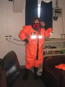 Sue posing in bulky orange body suit