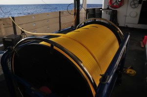 Cylander with a yellow hose-like cable wrapped around it sitting on the deck.