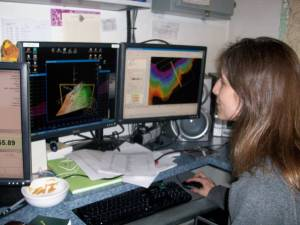 "In this picture I'm attempting to clean ""dirty"" data.  The screen on the left shows a 3D image of the ocean floor.  The screen on the right shows a 2D image of the ocean floor that is color coded based on depth. As you can see, dirty dishes also tend to collect when cleaning dirty data!"