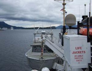 A small boat called a launch with a view of the mountains in Ketchikan, from the RAINIER