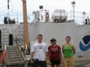 NOAA Teacher at Sea, Lisha Hylton (center), stands in front of the DELAWARE II with some fellow ship mates.