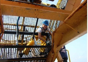 I am wearing my bib and overalls, boots, and a hardhat while working inside the dredge to free the clams caught in the corners and cracks of the dredge.