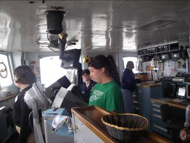 In the pilot house on the NOAA Ship RAINIER, from left to right, ENS Olivia Hauser, RAINIER Junior Officer,  ENS Megan McGovern, RAINIER Junior Officer,  Umeko Foster in foreground Intern, and Jacquelyn Hams, TAS on far right.