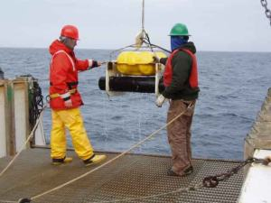 Crewmembers retrieve a marine mammal listening device from the water.