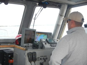 The coxswain navigating with data from the survey team, AIS, etc.