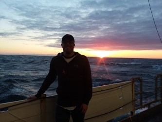Me standing on the deck of NOAA ship Bigelow in front of a sunrise