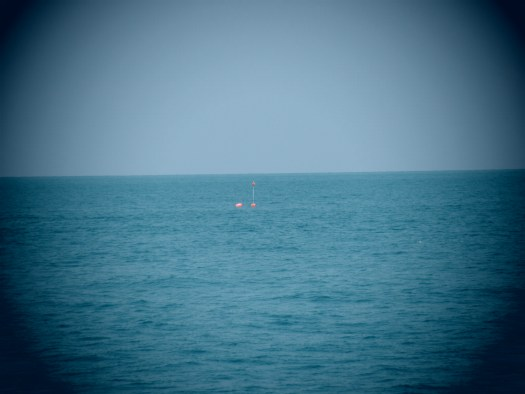 A high flyer and buoy float on the surface of the water.