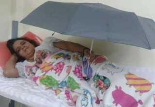 Paciente se protege das goteiras utilizando guarda-chuva