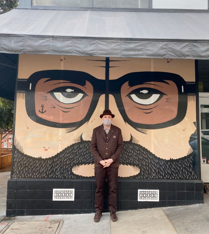 Artist Jeremy Fish (in a custom Ben Davis costume) poses near his mural and the North Beach (formerly French Italian Bakery) studio on Grant Avenue.