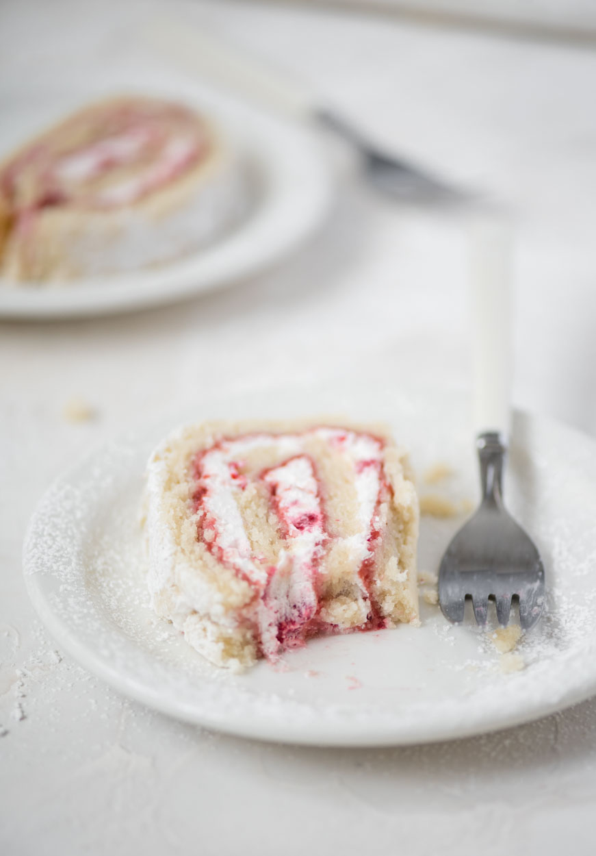 A beautiful slice of raspberry lemon roll with a bite taken out of it
