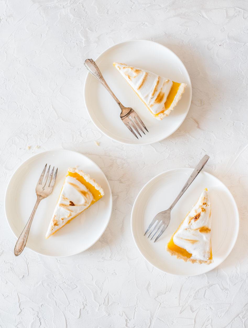 top down view of 3 lemon meringue pie slices on white plates
