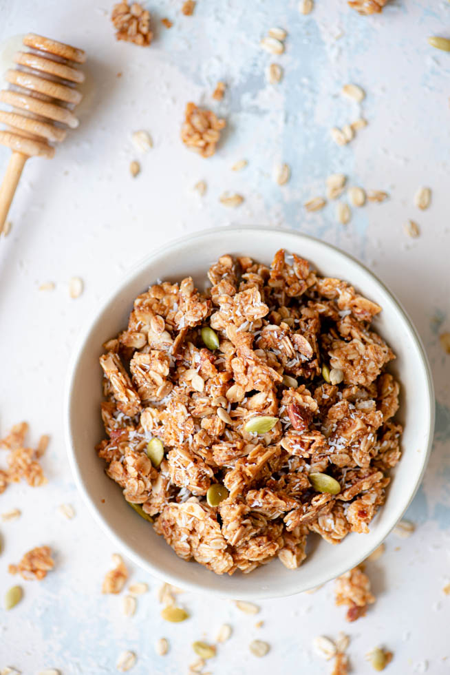 top down view of homemade granola with coconut pumpkin seeds almonds honey