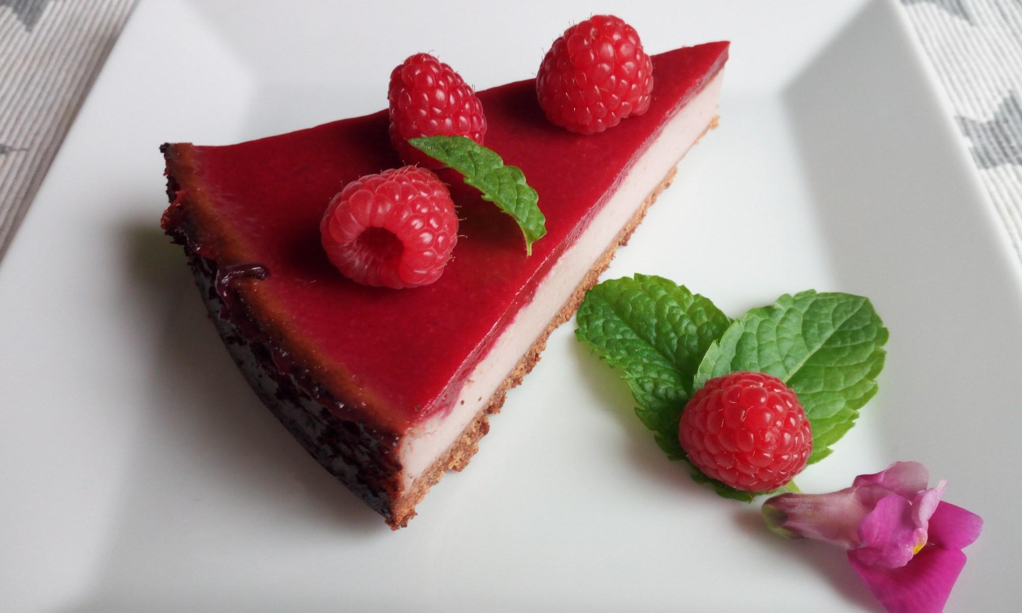 Käsekuchen - Vegan: Ein viereckiger weißer Teller mit einem spitzen Kuchenstück, dass aus weißer Sojacreme besteht und mit einer knallroten Himmbeerlasur überzogen ist. Garniert mit Minzblätter und Himbeeren.