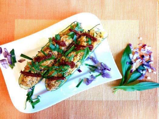 Ein rechteckiger weißer Teller mit 2 gebackene halbe Zucchini gefüllt mit Bulgur-Tomaten-Gemisch und Basilikum