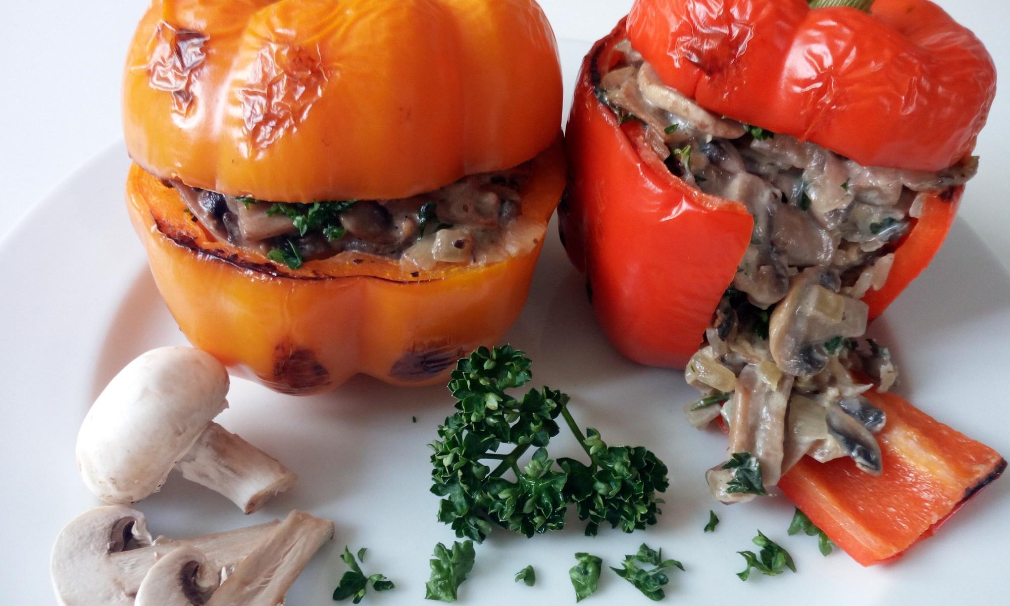Zwei (gelb und rot) angebratene Paprika, die mit einer Champignon-Linsen-Reis-Rahm - Füllung, garniert mit Petersilie