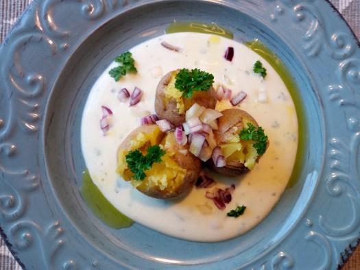 Blauer großer Teller mit gekochten, leicht aufgebrochenen, Kartoffeln mit Schale in Soja-Joghurt mit Petersilie, Schnittlauch, kleinen roten Zwiebelwürfel und kalt gepresstesLeinöl