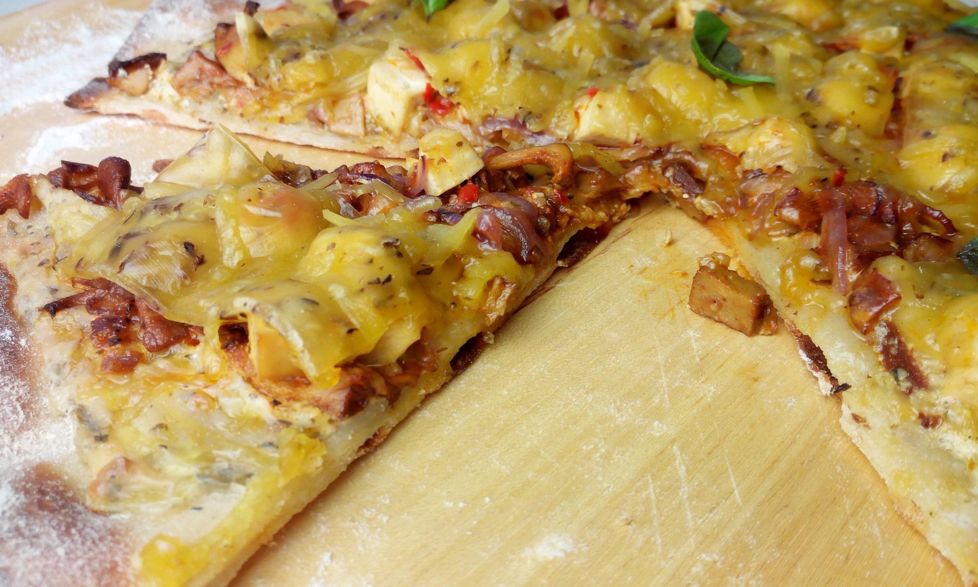 Die herzhaft deftige Pizza mit Pfifferlinge, geschmolzenem veganen Käse, roten Zwiebeln, leckerer pflanzlicher Käsecreme, Fermento Tofu-Würfeln und frischen Basilikum