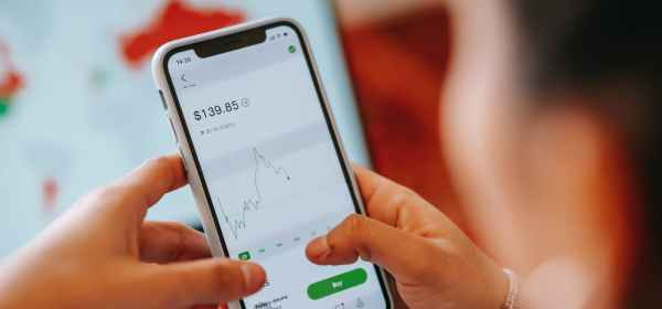 crop dealer touching screen on smartphone with trading application